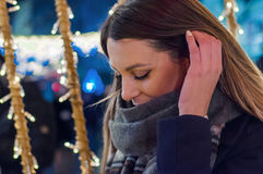 Lonely Christmas woman on the winter street at night. Festive br. Unette feeling sad at christmas looking up royalty free stock image