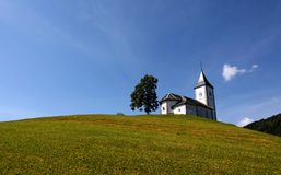 Lonely church on a hill. Lonely church and a tree on a hill Royalty Free Stock Image