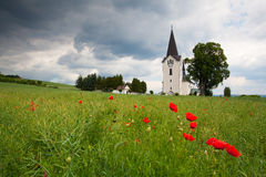 Lonely church in the middle poppy field Stock Photos