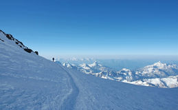 Lonely climber over the mounts. Lonely climber over the mountain peaks ascending the Elbrus, highest peak in Russia, Caucasus Stock Photography