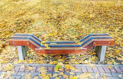Lonely colorful wooden bench in park in the autumn. With yellow maple leaves around stock photography