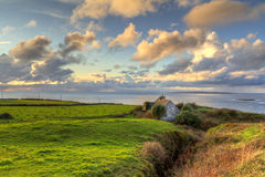 Lonely cottage house at the ocean. Irish cottage house near the ocean at sunset Royalty Free Stock Images