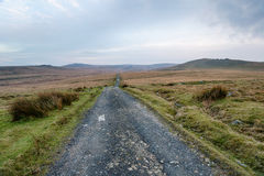 Lonely Country Road. A lonely country lane leading through bleak moorland at Okehampton Camp on Dartmoor National Park in Devon Royalty Free Stock Photo