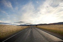 Lonely country road. Wide angle view of Lonely country road with beautiful clouds stock photos