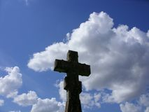 Lonely cross against summer sky. Stone cross at an old graveyard on beautiful summer sky background Royalty Free Stock Photo