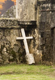 Lonely Cross Against Wall. An almost white crucifix, pulled from the ground, is leaning against the walls of an old abandoned building that is slowly crumbling stock photography