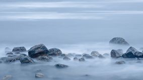 Lonely cross in the fog in a pile of wet stones royalty free stock image