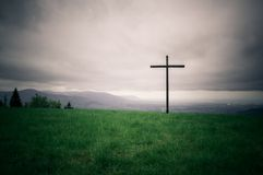 Lonely cross on the horizon series. Lonely cross series. A wooden cross on a hilltop horizon background. Symbol of Christianity under a heavy sky royalty free stock photography