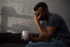Lonely crying man holding cup of coffee sitting. At home royalty free stock photos