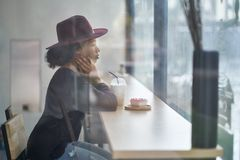 Beautiful girl in cafe. Lonely curly girl sits in a cafe and looks in the window. There is a cocktail and a cake on the table in front of her. She wears a dark Royalty Free Stock Images