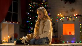 Lonely cute girl with teddy-bear sitting near Christmas tree, missing parents. Stock photo royalty free stock photography