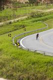 Lonely cyclist doing curve in highway sidelined by green vegetat Royalty Free Stock Photos
