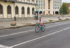 Lonely cyclist on Yavornytskyi Avenue at summer weekend in Dnepr city. Dnepr, Ukraine - August 24, 2016: Lonely cyclist on Yavornytskyi Avenue at summer weekend royalty free stock photography