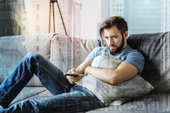 Disappointed depressed man lying and holding the control desk. Lonely day. Disappointed unshaken depressed man lying on the sofa hugging the pillow and holding Stock Image