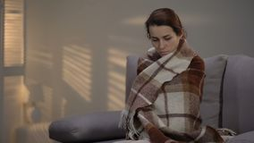 Lonely depressed female sitting on couch, covered with plaid, unemployment stock footage