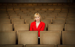 Lonely, depressed woman sitting alone in empty  theater Stock Photography