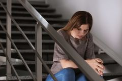 Lonely depressed woman sitting on stairs royalty free stock images