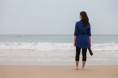 Lonely and depressed woman standing in front of the sea Stock Images