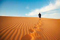 Lonely in desert. Young man is running to the top of dune in desert Royalty Free Stock Photos