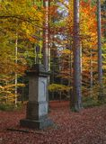 Lonely deserted stone memorial monument with cross  in autumn co. Lored orange beech tree forest Stock Photo