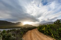 Lonely dirt road leading into a mountain range at sunset. Lonely dirt road winding into the mountain range at sunset in cape town south africa Royalty Free Stock Photos