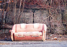 Lonely dirty abandoned sofa, left in the street Royalty Free Stock Images