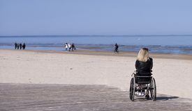 Lonely disabled young woman on beach. Sunny summer day royalty free stock photography