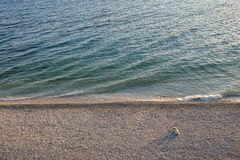 Lonely dog on a beach. Minimalistic composition of a lonely dog lying on a beach during sunset seen from above Stock Photo
