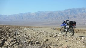 Lonely dual sport motorcycle on empty dirt road in Death Valley desert in United States. Lonely dual sport motorcycle on empty dirt road in Death Valley in stock photography