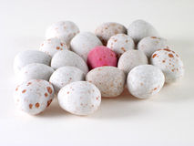 Lonely easter egg. Pink easter egg surrounded by white ones (Foreground eggs are in focus royalty free stock photo