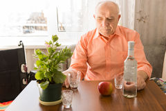 Lonely Elderly Drinking Wine at the Wooden Table Royalty Free Stock Image