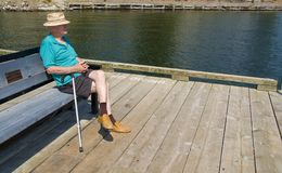 Lonely elderly man. Seated on bench Royalty Free Stock Image