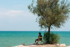 Lonely elderly man sitting by the sea stock images