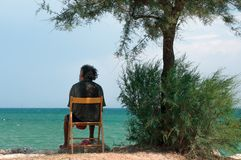 Lonely elderly man sitting by the sea stock image