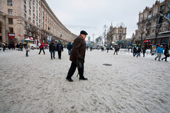 Lonely elderly man walk down the snow street Royalty Free Stock Image