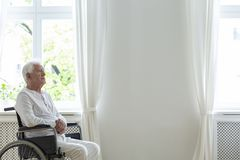 Lonely elderly patient in a wheelchair in a white room next to an empty wall. Place your logo royalty free stock photos