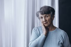 Elderly person suffering from Alzheimer. Lonely elderly person suffering from Alzheimer lost at home royalty free stock photography