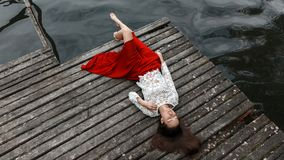 Lonely european girl in red skirt on the bridge. A girl with closed eyes in a red skirt is lying on the bridge Stock Image