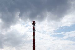 Lonely factory chimney against dark cloudy sky Stock Images