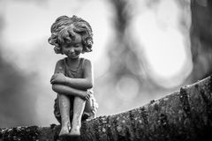 Lonely fairy in mono. A fairy statue alone sitting in a tree Royalty Free Stock Photo