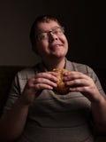 Lonely fat guy eating hamburger. Bad eating habits. Royalty Free Stock Photo