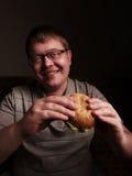 Lonely fat guy eating hamburger. Bad eating habits. Stock Images