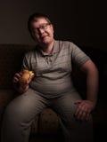 Lonely fat guy eating hamburger. Bad eating habits. Stock Photography