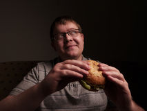 Lonely fat guy eating hamburger. Bad eating habits. Royalty Free Stock Images