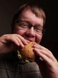 Lonely fat guy eating hamburger. Bad eating habits. Closeup. Stock Image