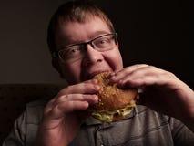Lonely fat guy eating hamburger. Bad eating habits. Closeup. Stock Images