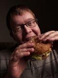 Lonely fat guy eating hamburger. Bad eating habits. Closeup. Stock Photography