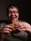 Lonely fat guy eating hamburger. Bad eating habits. Closeup. Royalty Free Stock Photo