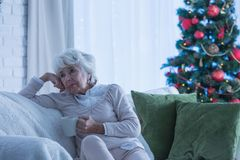 Lonely female senior during christmas. Lonely senior citizen sitting on the couch during christmas royalty free stock photos