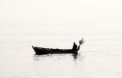 Lonely fisherman. Fisherman fishing alone on  misty day, silhouette Stock Photography